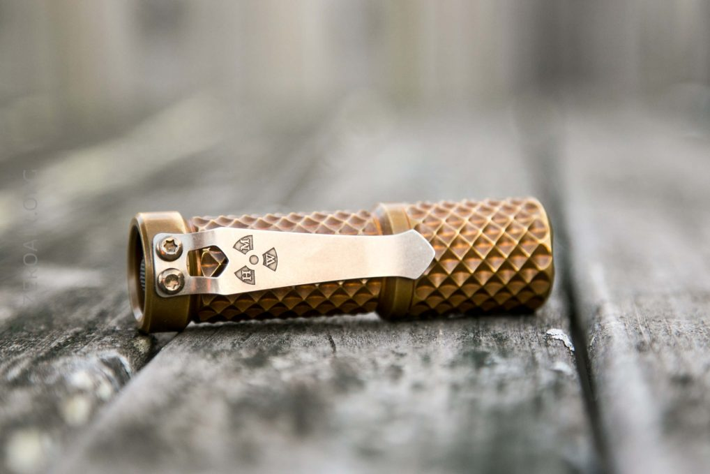 hanko trident total tesseract brass flashlight laying on side showing steelflame pocket clip