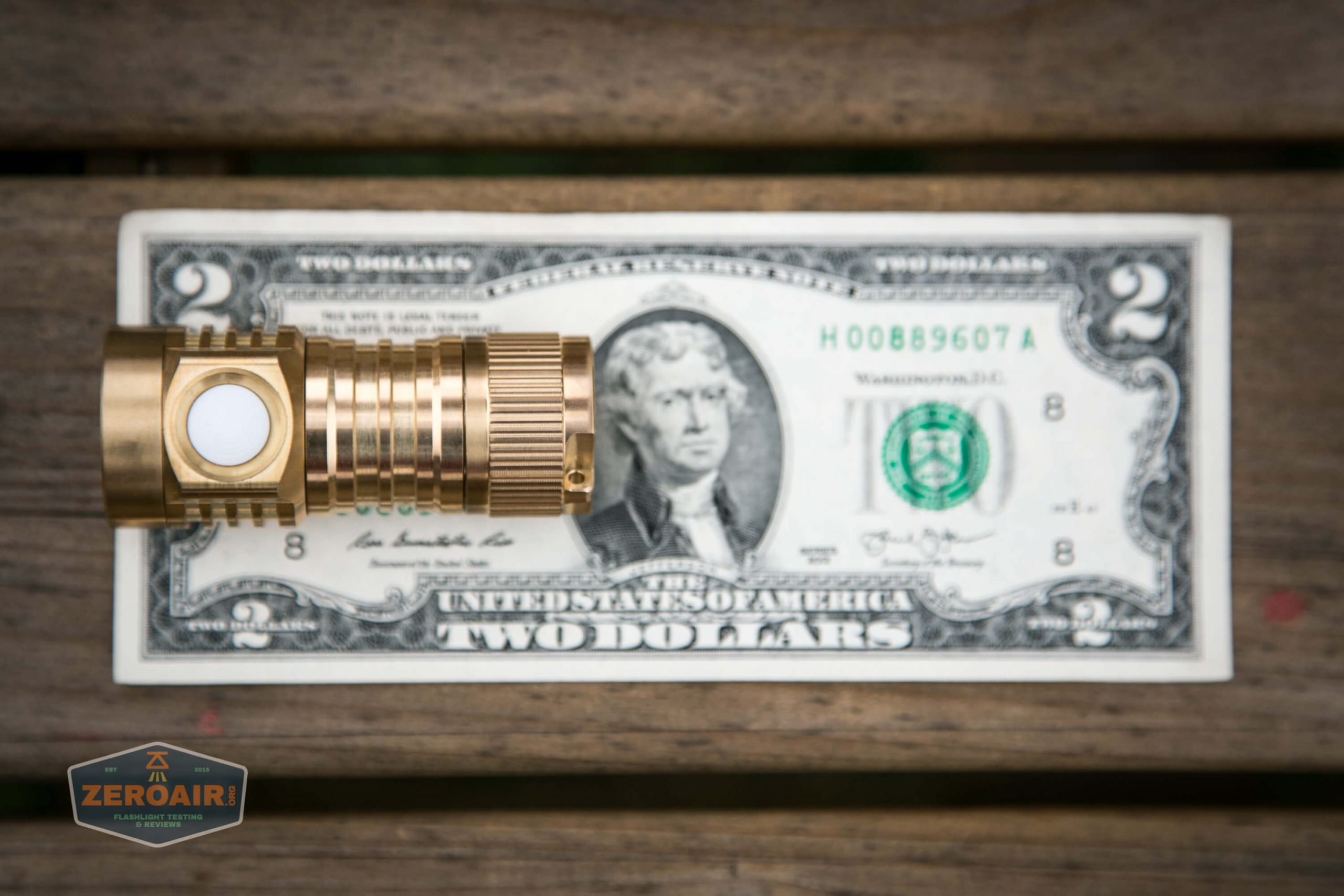 emisar d4v2 brass flashlight nichia e21a 4500K on two dollar bill