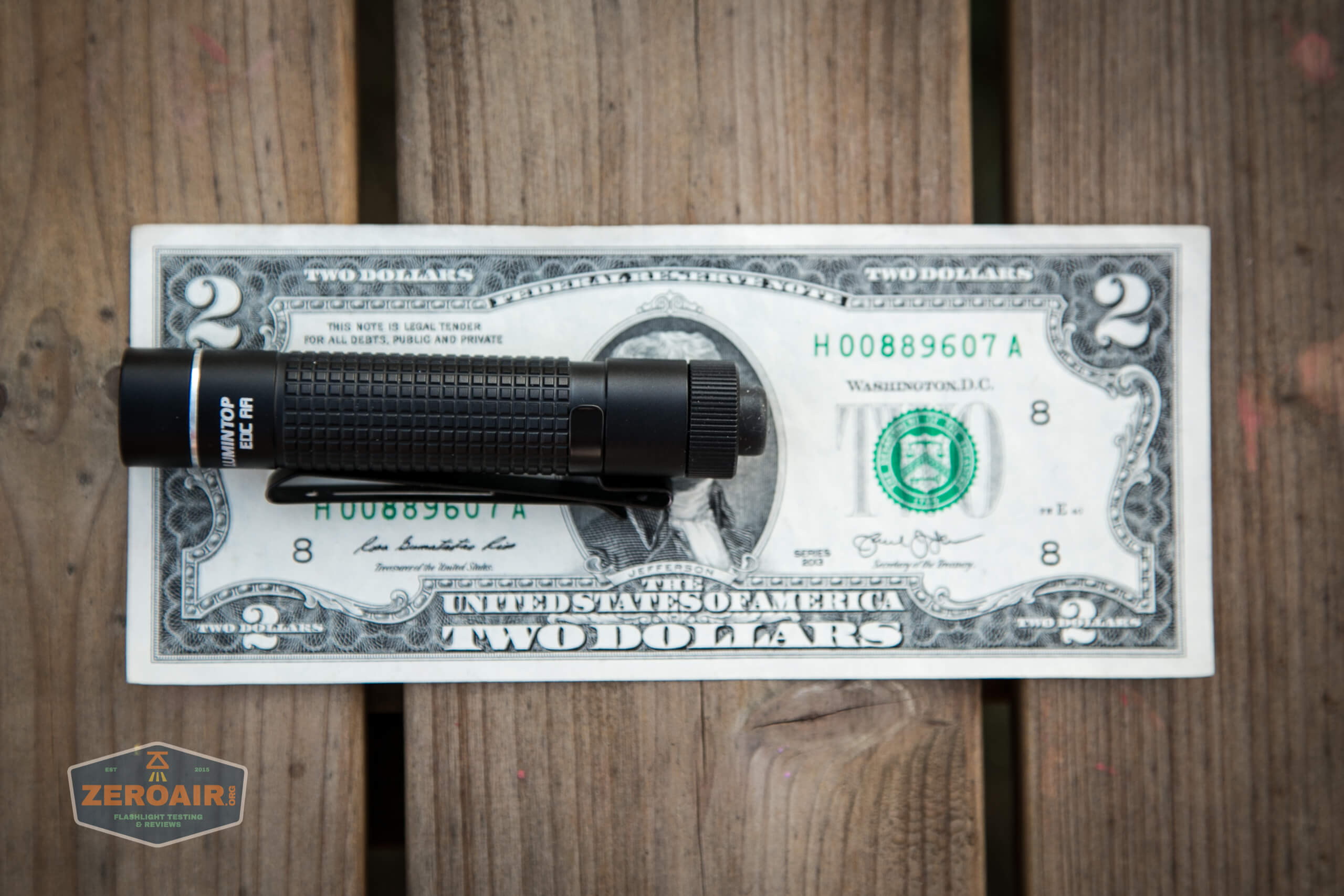 lumintop edc aa flashlight on two dollar bill