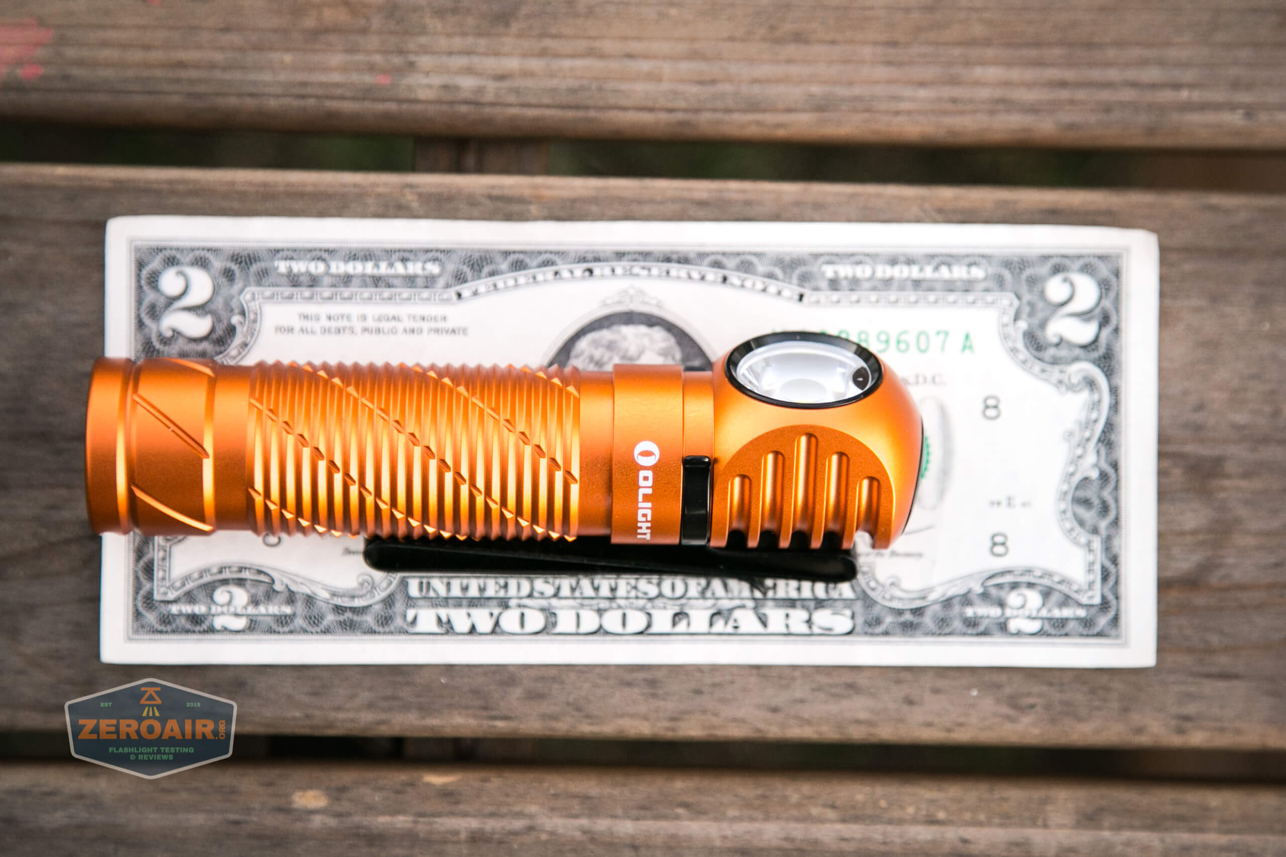 olight perun 2 21700 headlamp orange on two dollar bill
