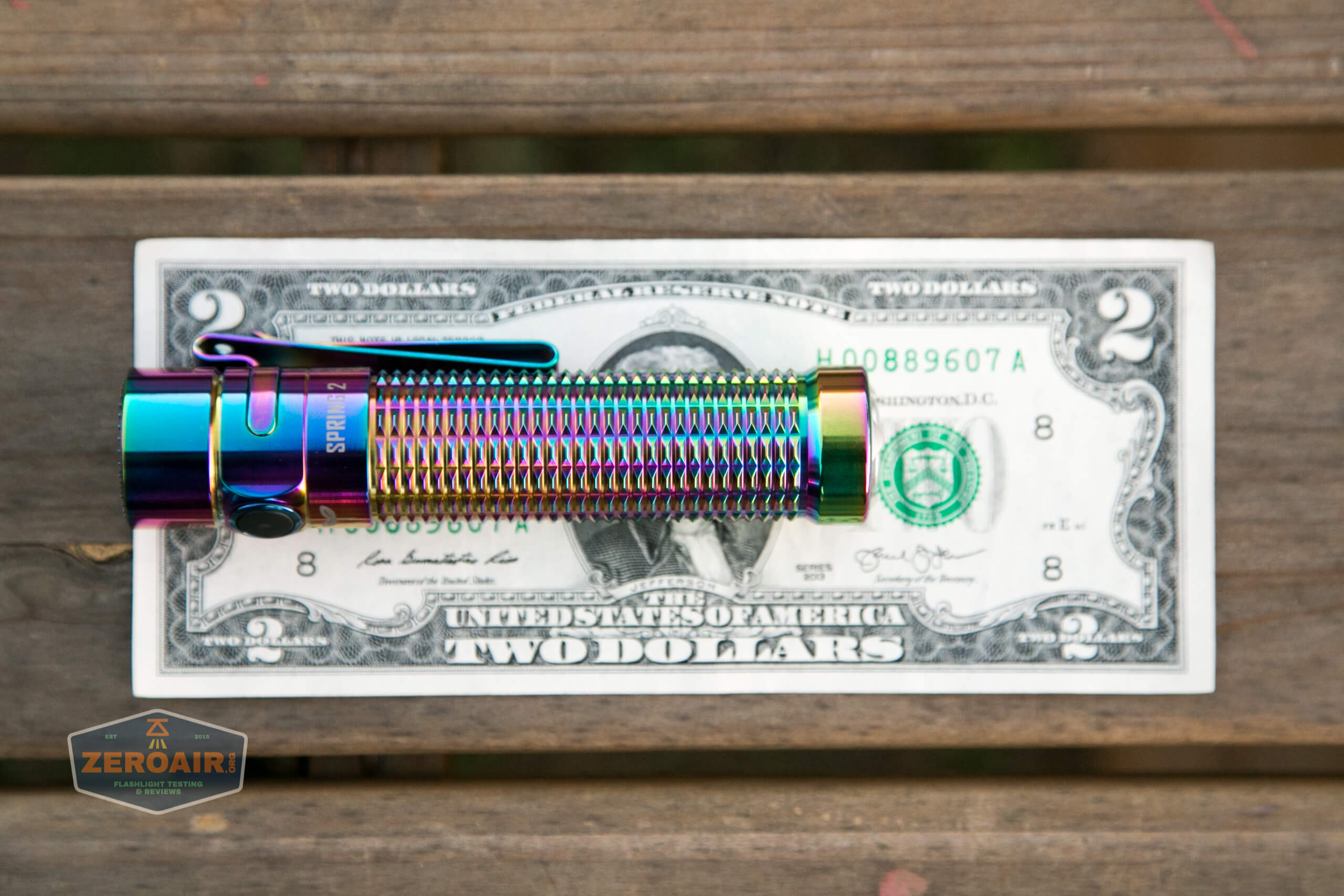 olight warrior mini rainbow spring 2 led flashlight on two dollar bill