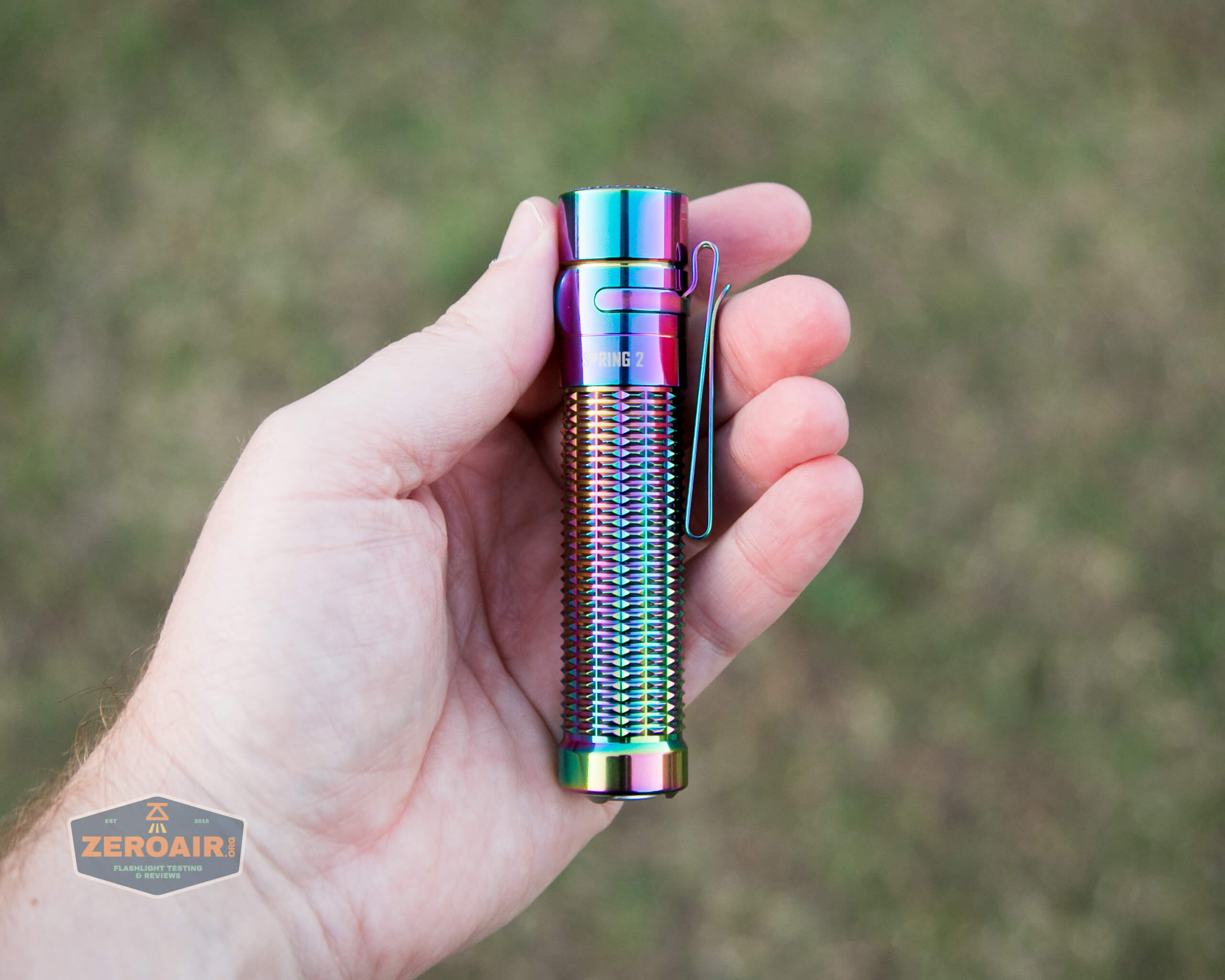 olight warrior mini rainbow spring 2 led flashlight in hand