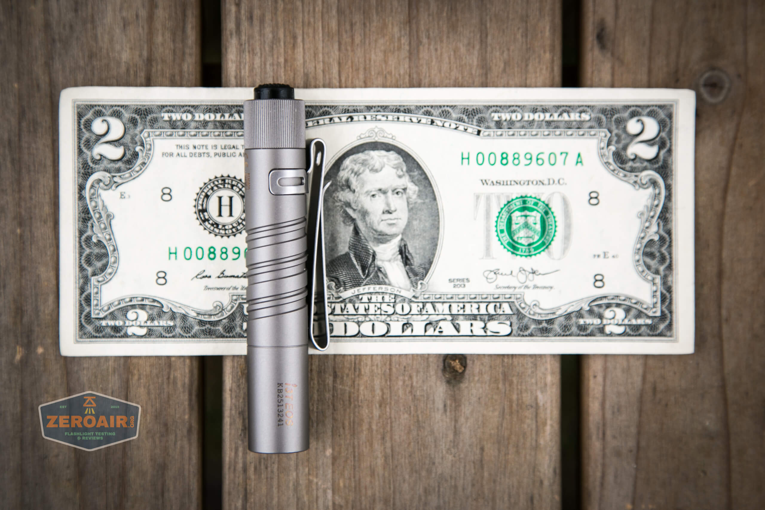 olight i3t eos titanium aaa flashlight on two dollar bill