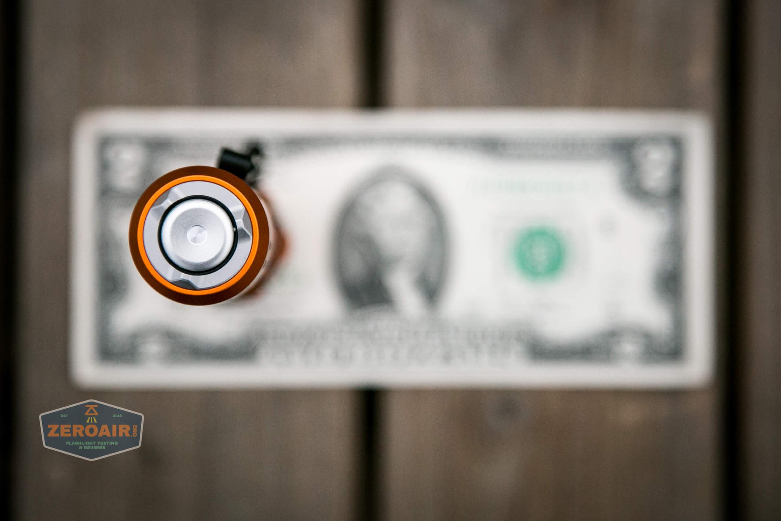 Olight M2R Pro Warrior Orange on two dollar bill