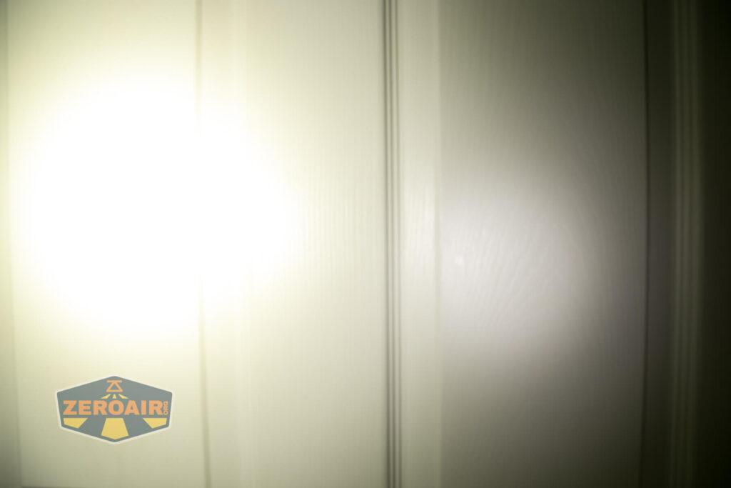 Acebeam X50 Searchlight beamshot on door, compared to nichia 219b