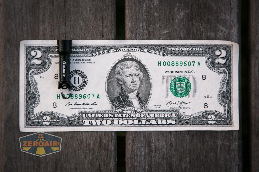 Olight X9R Cell on two-dollar bill